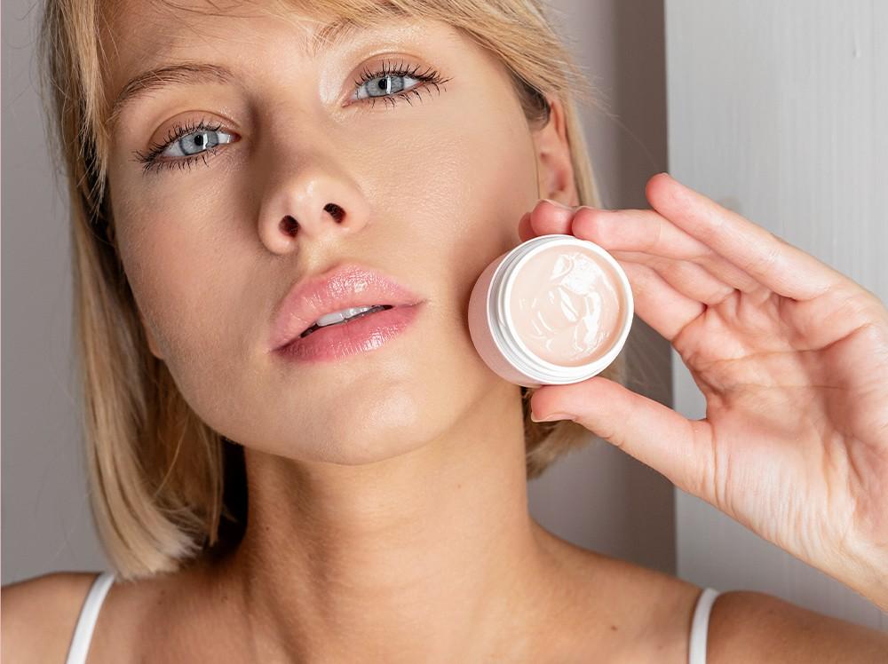 modelka ze słoiczkiem balsamu przy twarzy