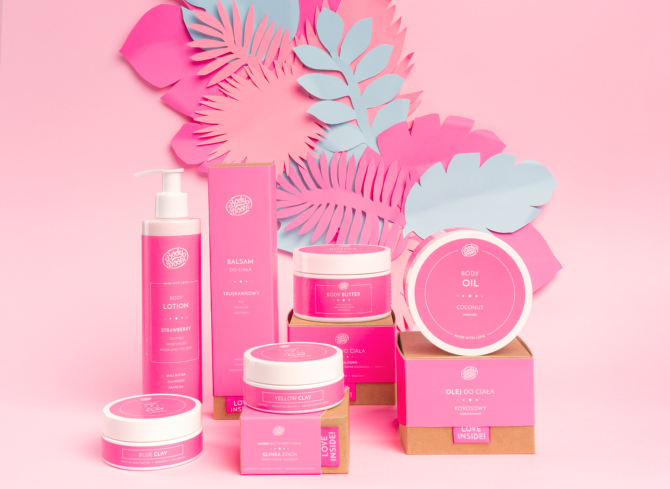 różowe liście wycinane z papieru i kosmetyki w różowych opakowaniach
