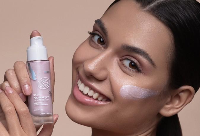 młoda uśmiechnięta dziewczyna trzymająca bazę pod makijaż