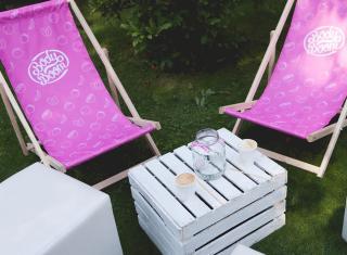 Różowe drewniane leżaki z nadrukiem rozłożone na trawie obok białego stolika z drewnianej skrzynki