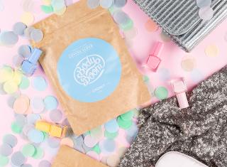 peeling kawowy na tle konfetti, cekinowej sukienki i srebrnej torebki z pastelowymi lakierami do paznokci