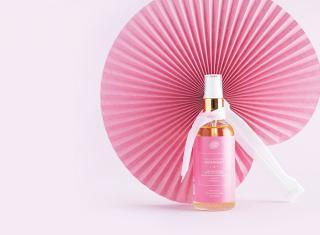 butelka olejku na różowym tle