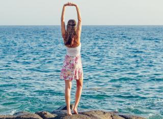 kobieta zwrócona do morza stojąca tyłem i wyciągająca ręce do góry