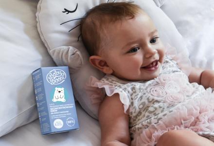 szcześliwy niemowlak na łóżku z kremem do pielęgnacji ciała
