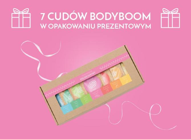 pudełko prezentowe z rozwiązaną różową wstążką, w środku 7 peelingów z kolorowymi etykietami