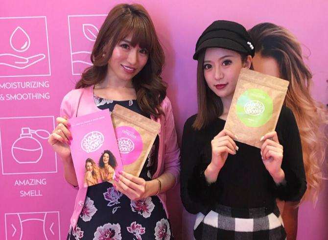 dwie uśmiechnięte azjatki na stoisku targowym marki kosmetycznej