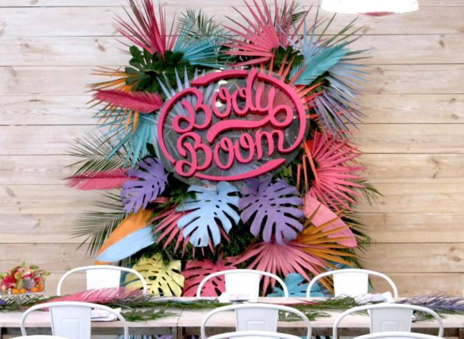 logo na tle liści egzotycznych pomalowanych na kolorowo