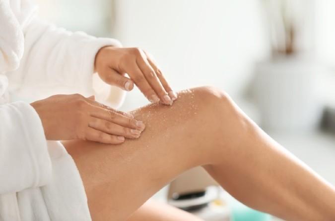 dziewczyna złuszczająca nogi peelingiem
