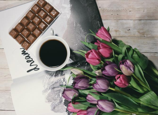 Tabliczka czekolady i filiżanka kawy położona na gazecie, obok różowe tulipany