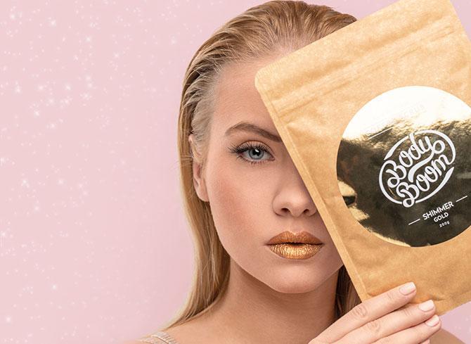 Modelka trzymająca w dłoni opakowanie peelingu kawowego