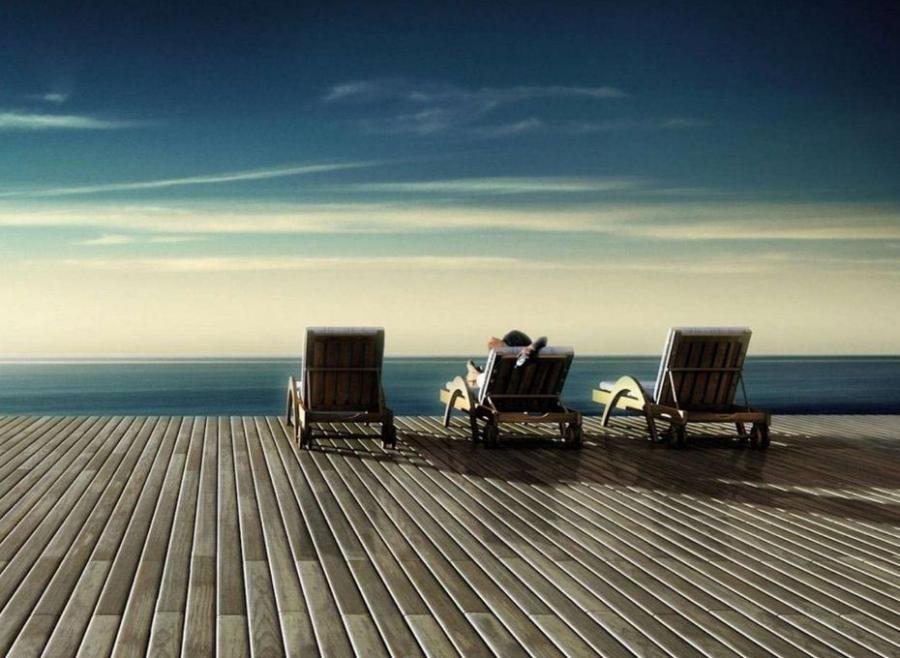 drewniany taras z widokiem na ocean z leżakami