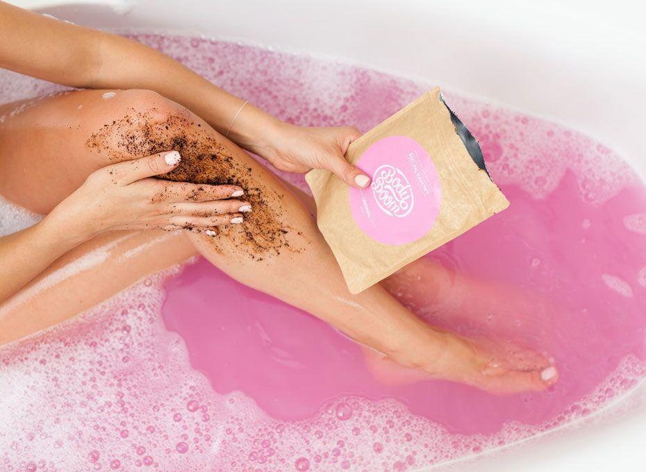 Kobieta podczas kąpieli rozprowadza peeling kawowy na nodze