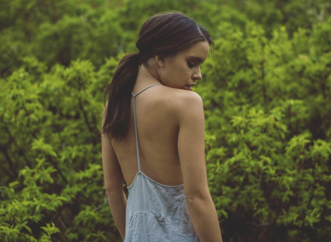 kobieta w błękitnej sukience na ramiączkach na tle lasu