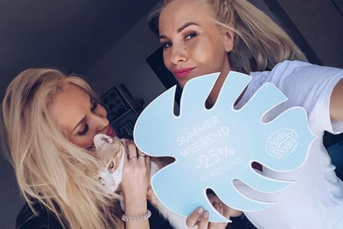 Dziewczyny trzymające w dłoni kota oraz liść z zapowiedzią promocji