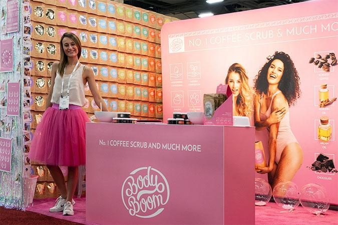 Dziewczyna w różowej spódnicy na wielobarwnym stoisku na targach kosmetycznych