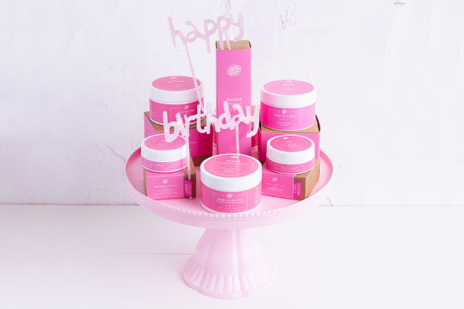 Ułożone kosmetyki z z napisem Happy Birthday w tle