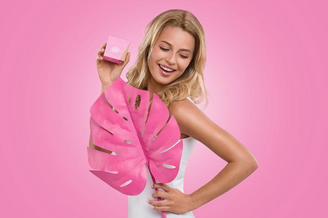 Blondynka trzymająca w dłoniach opakowanie kosmetyku