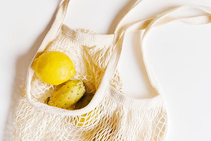 Ekologiczna torba z cytrynami na białym tle